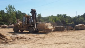 A tractor moves raw stone in the quarry.